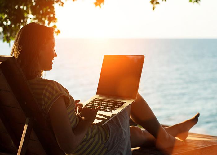 Vrouw met laptop op strand